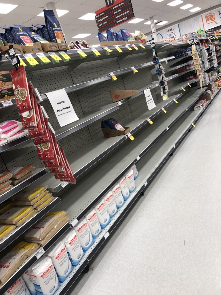 Picture of empty grocery store shelves with signs saying limit of 1 per customer